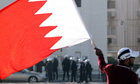 A Bahraini protestor waves his national flag in Sanabis