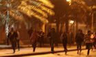 Anti-government demonstrators run from police in Manama, Bahrain
