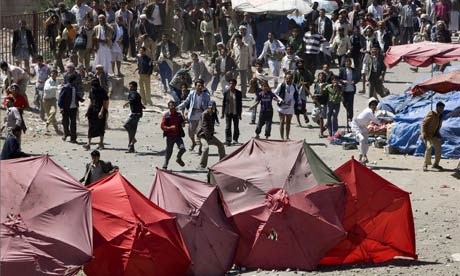 Pro-government supporters throw stones at anti-government demonstrators in Yemen