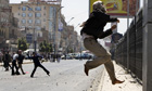 A Yemeni anti-government protester throws stones during clashes in Sana'a