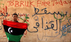 A Libyan anti-government protester holds a flag in Tobruk