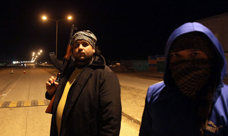 Libyan fighters patrol a street in Benghazi