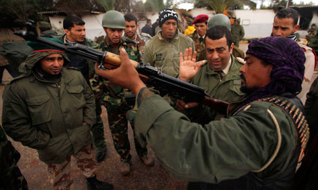 A rebel army officer teaches the use of a AK-47 to civilians  in Benghazi