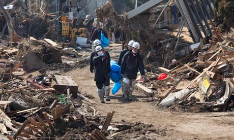 Rescuers carry a body away in Shintona, Japan