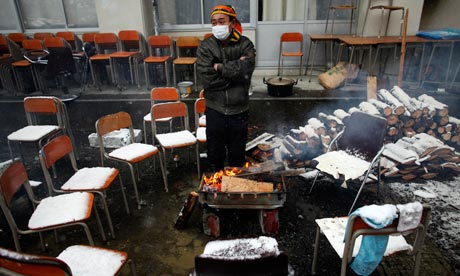 A survivor warms himself by a fire at an emergency shelter in Otsuchi
