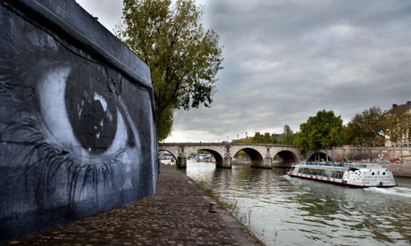 Photographs by JR are pasted on a wall of the bank of the River Seine