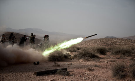 Libyan rebel fighters launch a rocket at  pro-Gaddafi forces at the front line near Gualish
