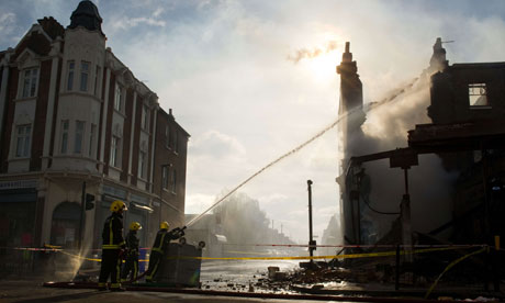 Firefighters spray the remains of a burnt-out shop after rioting on High Road in Tottenham