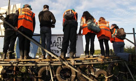 Activists and legal observers stand on barricades next to the main gate at Dale Farm travellers camp