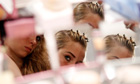 A model checks herself in a backstage mirror before the Tracy Reese Spring/Summer 2013 show