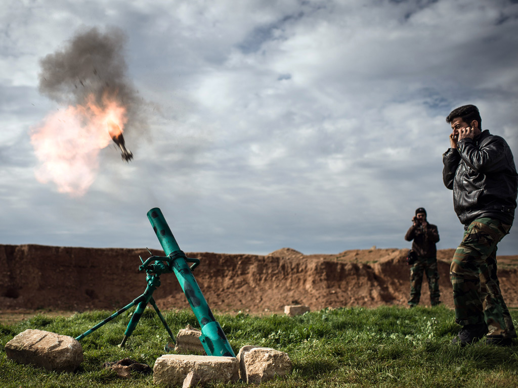 Syrian rebels fire a mortar