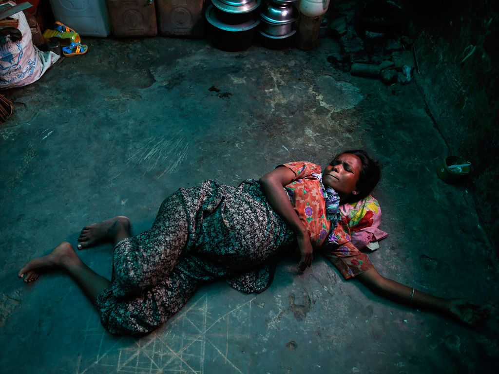 A pregnant Rohingya Muslim woman grimaces while experiencing labour pains at a shelter near Sittwe