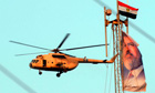 Egyptian military helicopter flies by the banner of the ouster Presided Mohammed Morsi in Cairo