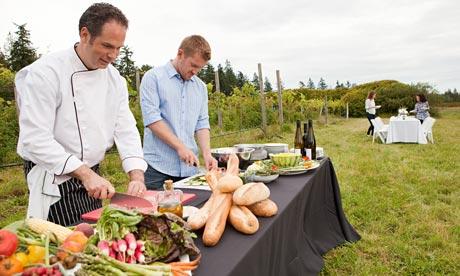 Men preparing food for dinner party in field