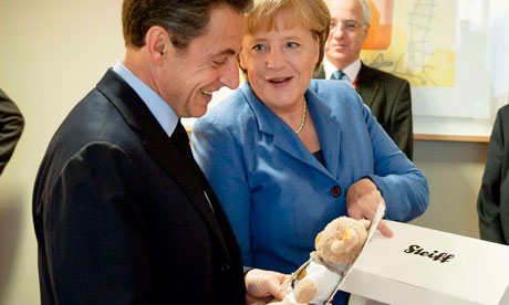 Angela Merkel presents a gift to Nicolas Sarkozy as she congratulates him on birth of daughter