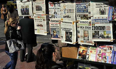 People look at newspapers headlines in Athens