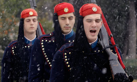 Greek presidential guards perform a change of shift during heavy snowfall in Athens.