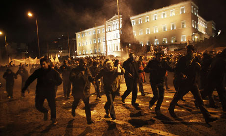 Protesters run away from teargas during clashes near the Greek parliament on February 12, 2012.