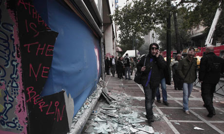 People walk past destroyed shops in central Athens on Monday February 13, 2012.