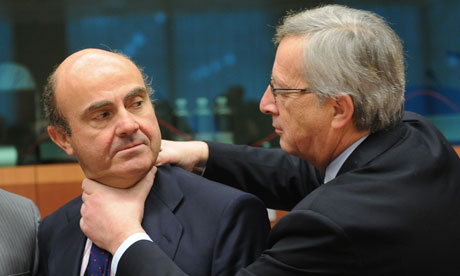 Jean-Claude Juncker, right, puts his hands on the neck of Spain's Economy Minister Luis de Guindos.