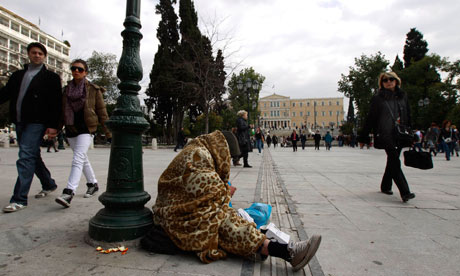 A homeless man begs at the central Syntagma (Constitution) Square, with the parliament behind.