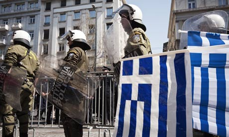 Riot police watch a Greek Independence Day military parade, 25 March 2012