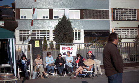 Workers take part in a one day strike in front of a banner reading