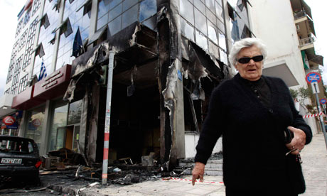 A woman walks in front of a damaged ministry building in Athens
