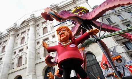 A puppet of German chancellor Angela  Merkel is hung in front of Milan's stock exchange.