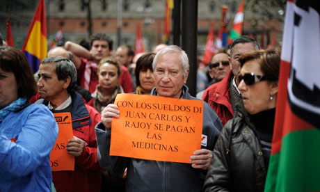 A protester carries a placard during a demonstration against government cuts in Bilbao