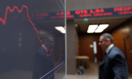 A man is reflected in the chart with stock prices at the Greek Stock Exchange in Athens.