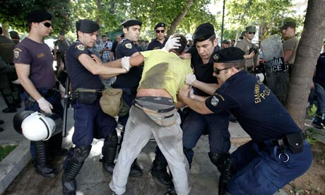 Police detain an anti-austerity protester in Athens