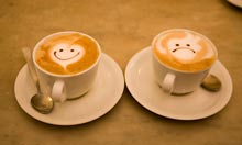 Happy and sad faces on cups of coffee