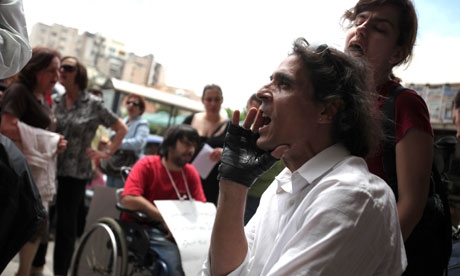 A man sitting in a wheelchair shouts slogans during a protest demanding welfare payments, in Athens