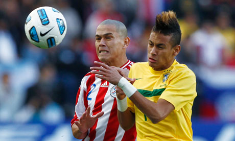 The Brazil striker Neymar challenges Paraguay's Dario Veron
