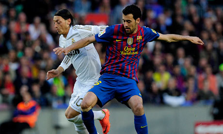 -Real Madrid's Mesut Ozil vies for possession with Barcelona's midfielder Sergio Busquets