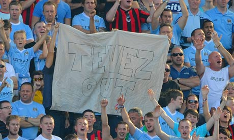 Manchester City fans hold up a banner proclaiming their feelings towards Carlos Tevez