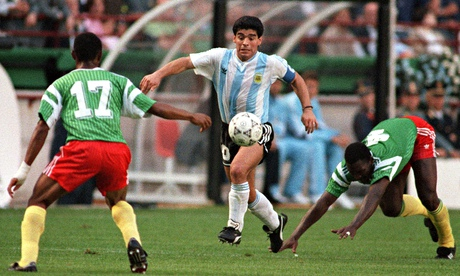 Argentina's Diego Maradona juggles with the ball as he runs past Cameroon's Benjamin Massing