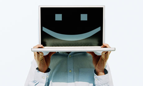 Man holding up laptop displaying smiley face