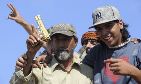 National Transitional Council fighters hold what they claim to be Gaddafi's gold-plated gun