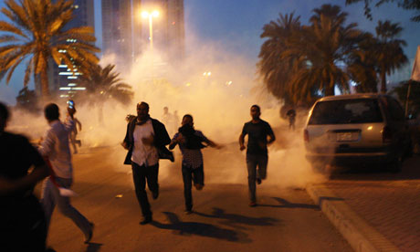 Protesters run from a cloud of teargas during a clash with Bahraini security forces