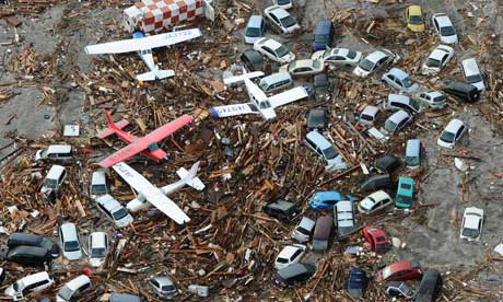 Light planes and vehicles swept from Sendai airport in northern Japan sit among the debris