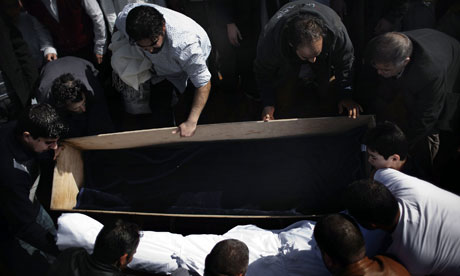 People lay down the body of a Libyan rebel killed the day before while defending Brega