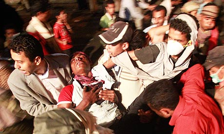 Yemeni protesters carry a wounded comrade during clashes with police in Taiz.