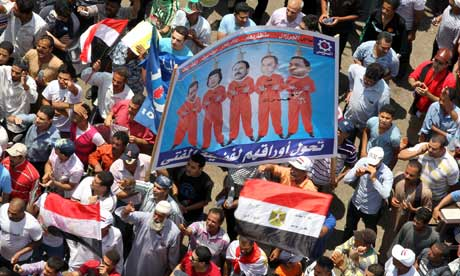 Egyptians display a placard depicting presidents