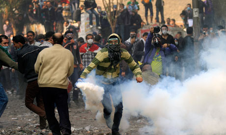A protester throws a teargas canister during clashes with Egyptian riot police at Tahrir square