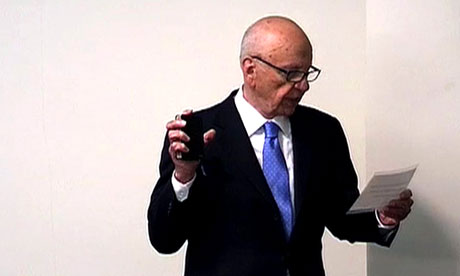 News Corp chief Rupert Murdoch swearing an oath holding a bible