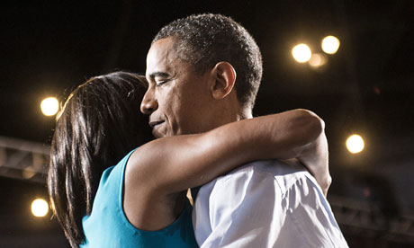 Barack and Michelle Obama embrace on stage