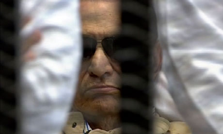 Hosni Mubarak is seen in the defendant's cage as a judge reads the verdict
