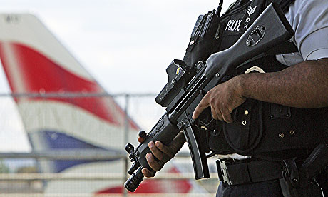 Armed British police officer patrols at Heathrow Airport
